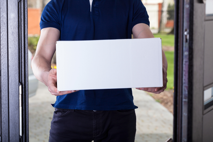 Courier with parcel standing in front of house