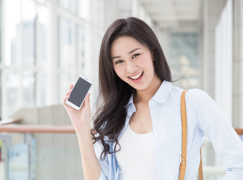 Happy young woman with her smart phone