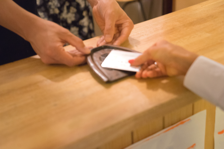 Detail of Japanese women making payment with credit card in a cafe.