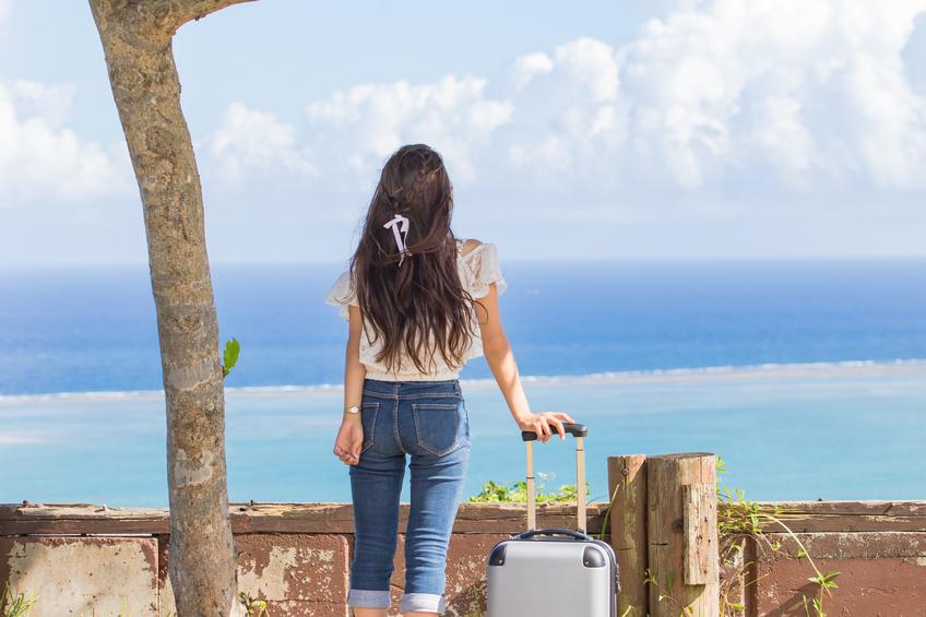 沖縄の海と旅をする若い女性