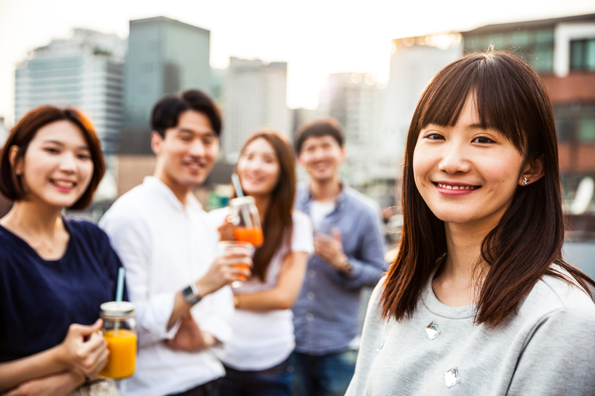 Friends having fun and greetings together starting a rooftop party in Seoul - Hondae district.