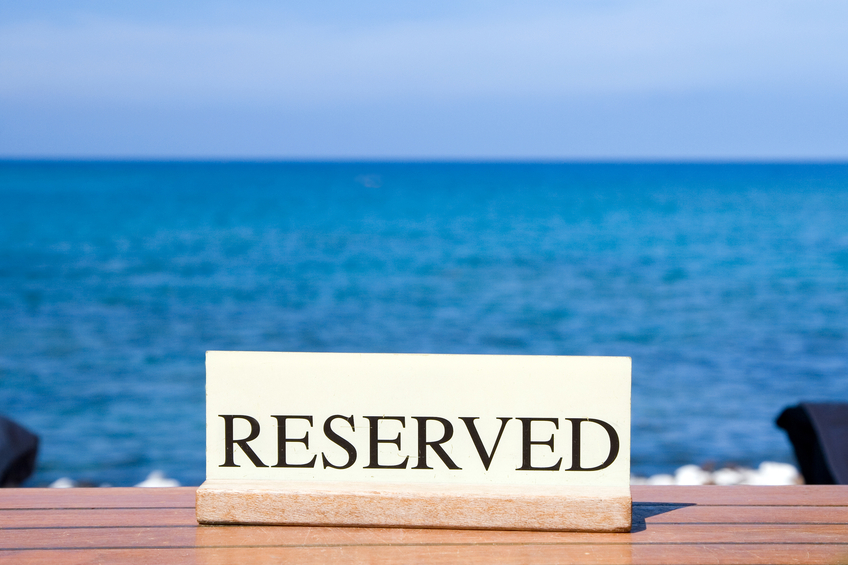 "Sign stating ""reserved"" overlooking ocean."