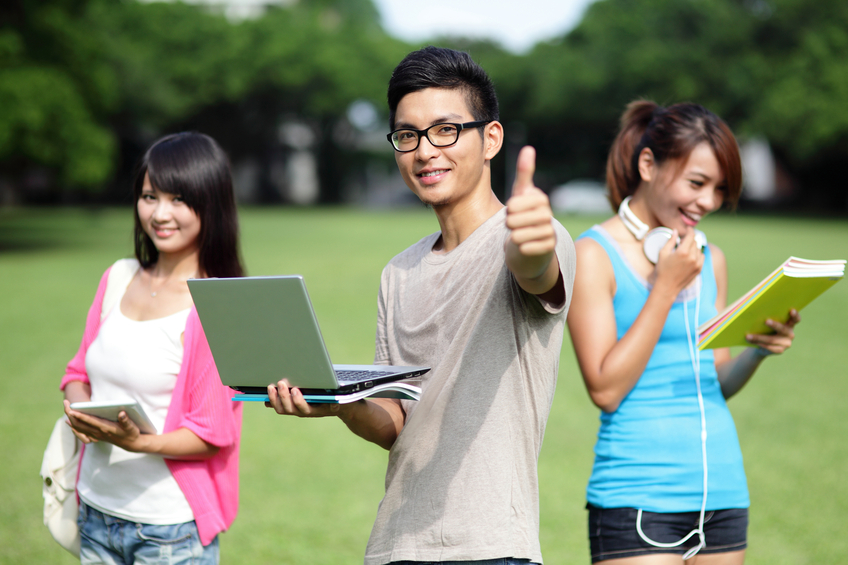 Happy College student man smile and show thumb up to you on campus lawn, asian